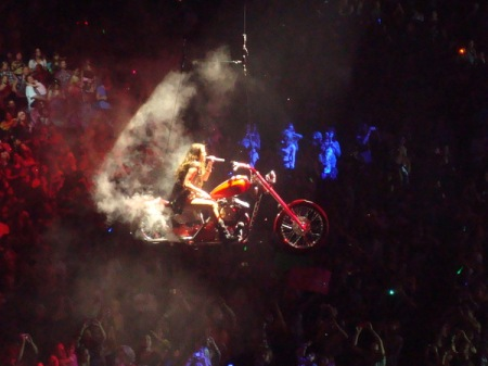 miley in the air on her motorcycle